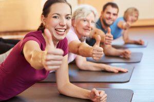 Lachende Gruppe hält die Daumen hoch im Sportstudio